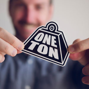 Mans fingers holding a sticker of the One Ton Logo