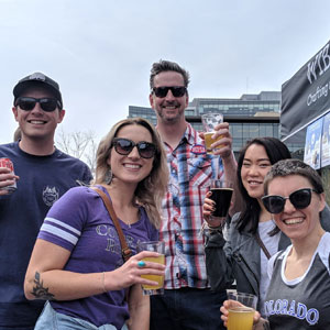 One Ton team members at a Colorado Rockies game posting for the camera with beers