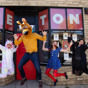 One Ton Team Members in Halloween Costumes jumping in the air outside of the One Ton Office
