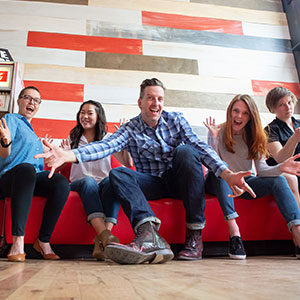 One Ton Team members sitting on a red bench making silly poses for the camera