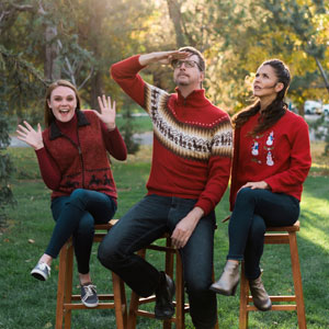 One Ton team members sitting on stools in a park making silly poses in red Christmas sweaters
