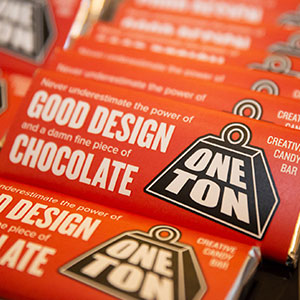 """Chocolate bars wrapped in a One Ton branded design that says """"Never underestimate the power of good design and a damn fine piece of chocolate"""""""