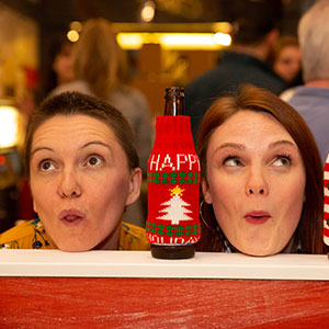 Two women making silly faces with their chins rested on a ledge with a bottle of beer in a happy holidays koozie between them