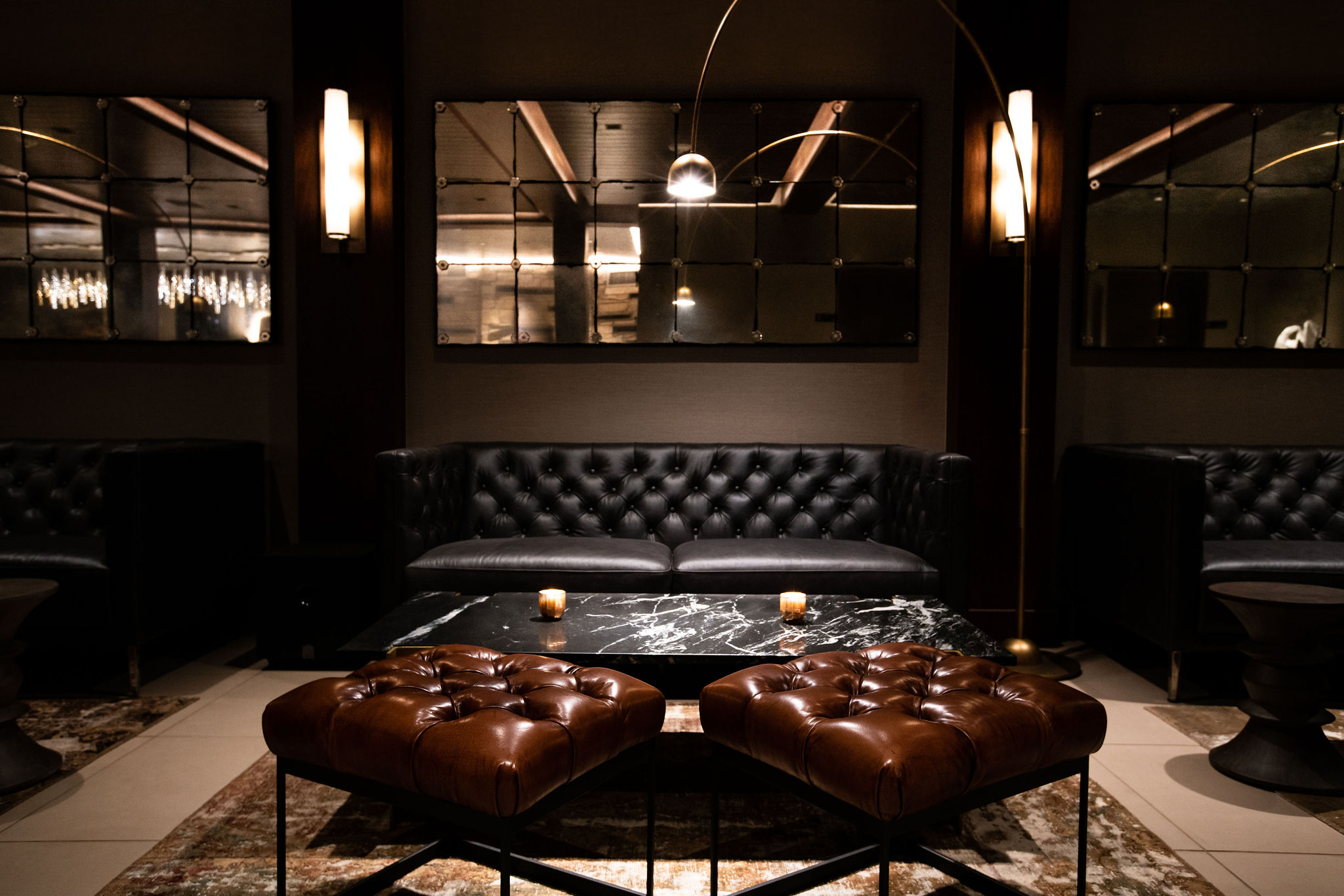 Interior of a high end cocktail lounge with leather couches and ottomans in a dimly lit room