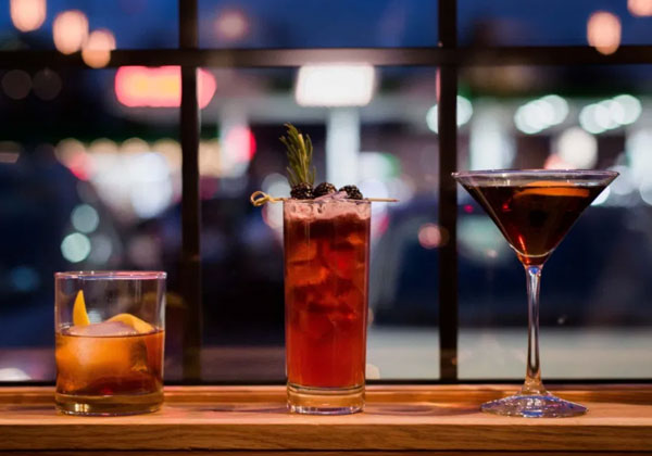 three cocktails lined up in front of a window with city lights shinging through