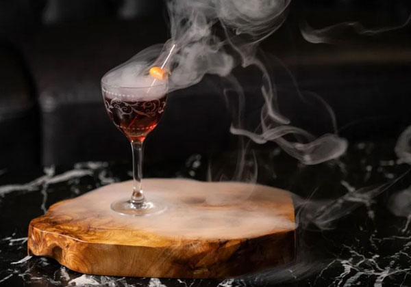 Cocktail with smoke coming from it sitting on a wooden coaster